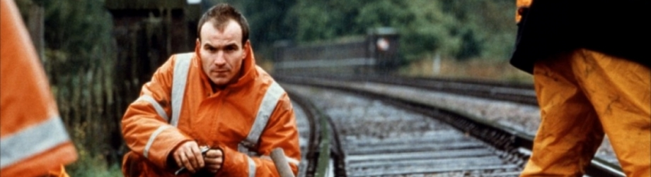 A man in an orange uniform kneels down on a train track with other men in the same uniform standing beside him
