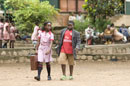A girl in uniform and carrying a case walks next to a boy in an Arsenal t-shirt