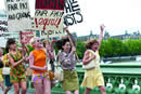 A group of women in 1960s dress run across a bridge smiling and holding placards reading 'fair pay'.