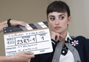 A dark haired female actor poses behind a pair of hands holding a clapperboard