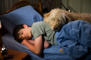 A teenage boy sleeps in his bed with a dog lying on top of the covers
