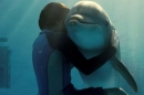 A young boy hugs a dolphin underwater