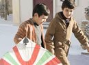 Two boys walk down a street, one carrying a large kite
