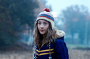 A medium shot of a teenage girl stood outside, wearing a wooly hat