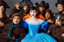 A young woman in a blue dress with seven dwarves standing around her.