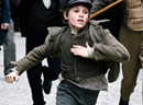 A young boy runs down the street with people chasing him