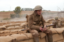 A soldier in WW2 uniform sits on sandbags at the side of a trench with his rifle on his lap