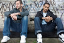 Two men sit on the floor leaning against a dirty graffiti wall