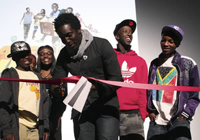 A man cuts a ribbon on stage, some teenagers stand behind him.