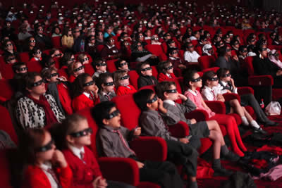 Wide shot of cinema auditorium full of shoolchildren waring 3D glasses