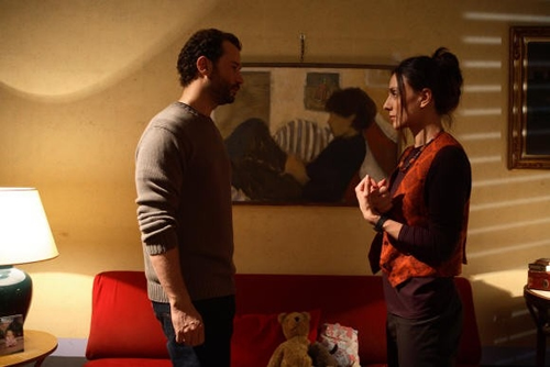 A man and a woman stand talking in a dully-lit room