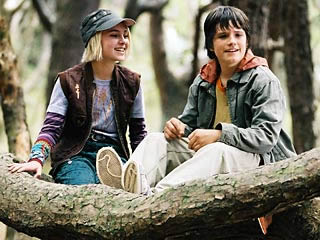 A boy and a girl sitting up a tree, looking below