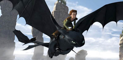 An animated dragon flies through the sky with a boy riding on top