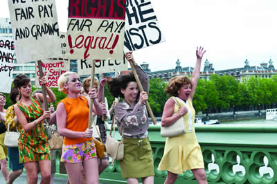 A group of women in '60s dress run across a bridge smiling and holding placards reading 'fair pay'.