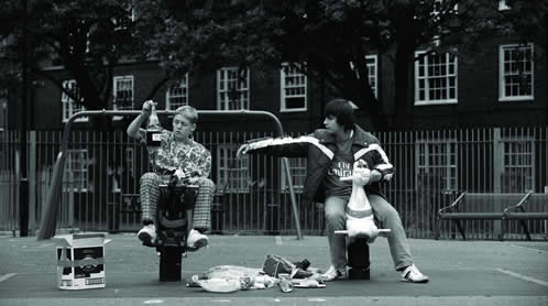 Two boys sit on toys in a public playground sharing a bottle of alcohol