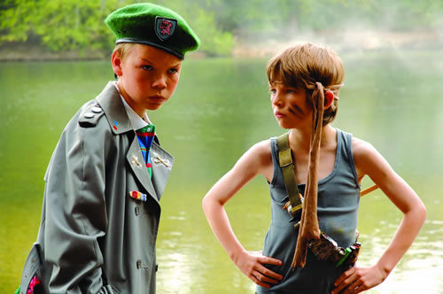 Two boys in military fancy dress stand by water