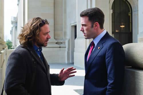 A man with long hair talks seriously to a smartly dressed man