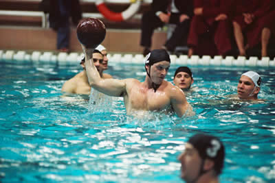 Men in swimming caps in a swimming pool throw a red ball