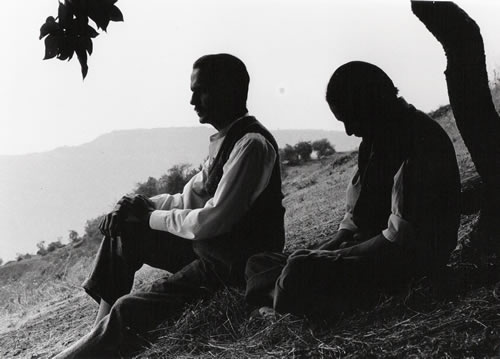 Black and white image of two men sat on a hill looking into the distance