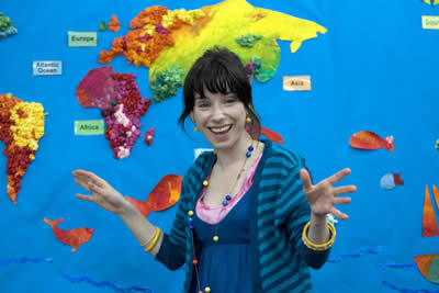 A woman smiles in front of a map of the world