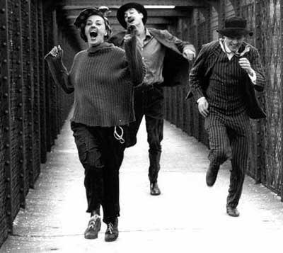 Black and white image of two men and a woman running towards the camera literally jumping with joy