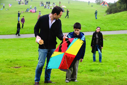 A man and a boy stand in a park holding a kite, a woman watches from further back