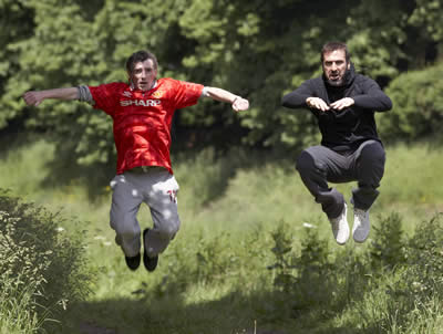 A teenager in a football shirt and a man in a hoodie jumping in the air surrounded by greenery