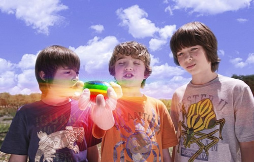 Three boys look at a bright rainbow object that one of them is holding