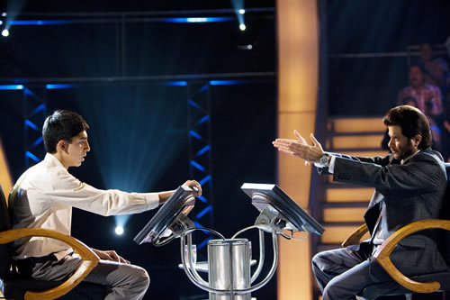 A boy and a man sit opposite each other in a game show television studio