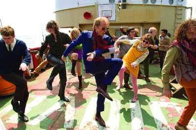 A group of people in brightly coloured clothing and sunglasses dancing on a boat