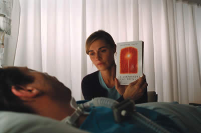 A man lying in a hospital bed, beside him a blonde woman holding a book up for him to see