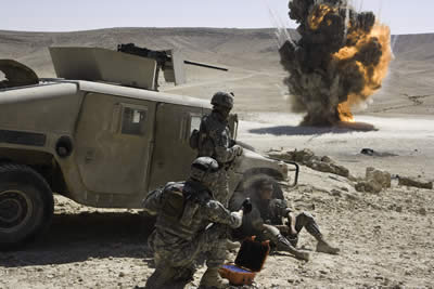 In the desert, an army truck and army men next to it in the foreground watching an explosion behind
