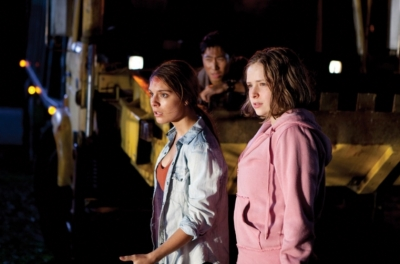 Two teenage girls stand in front of a truck with a teenage boy on the truck behind them