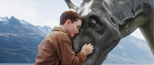 Close up of a boy hugging a horse's face