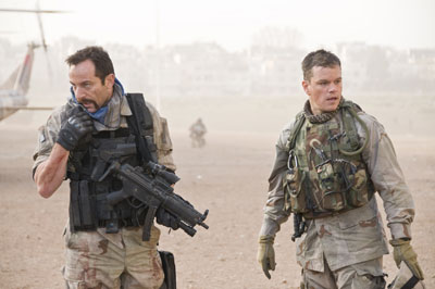 Two men in army uniform stand in the desert