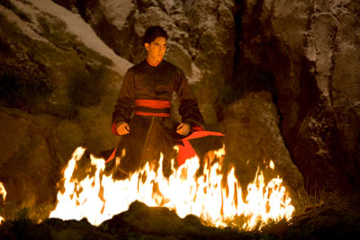 A man stands in a cave with flames around his feet
