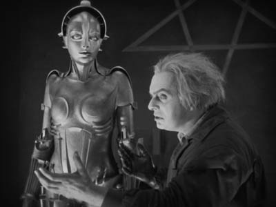a white-haired man stands before a female robot