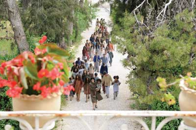 A woman carrying a child leads a group of children down a path