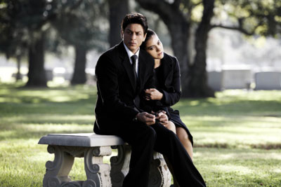 A man and a woman dressed in black sit on a bench