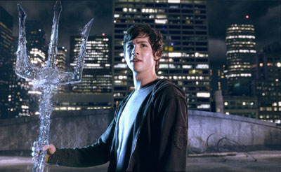 A teenage boys stands on a roof holding a trident made of water