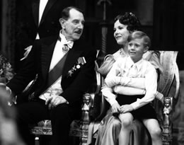 Still in black & white of a man sitting next to a woman with a boy on her lap