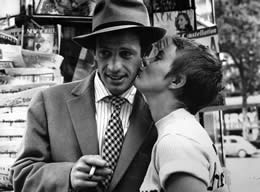 A girl kisses a man holding a cigarette on the cheek