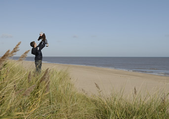 A teenage boy holds a baby in the air, stood on sand dunes, with the beach and sea in the background