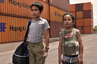 Two young boys stand side by side in a docking yard