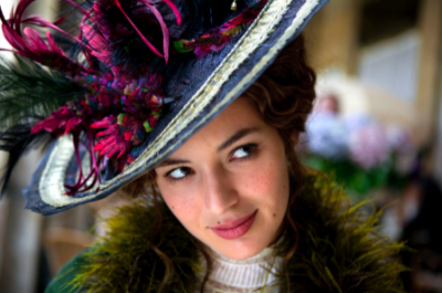 Woman looks up to the side whilst wearing a brightly coloured feather hat.