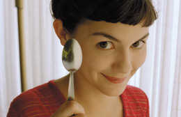 Close up of the face of a young woman holding a spoon