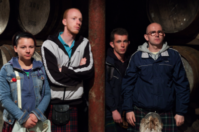 Three men and a woman all wearing kilts stand in front of some barrels