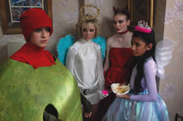 A girl looks embarrassed dressed as an olive at a fancy dress party with her friends dressed as fairies