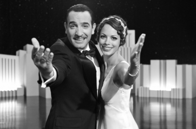A man in a tuxedo and a woman in a white dress stand on a stage with their arms outstretched towards the camera