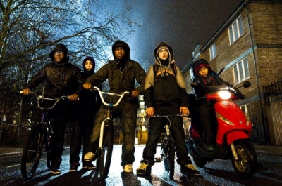 A group of teenage boys on bikes block the road into a housing estate